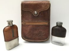 Two vintage leather and glass hip flasks, and a vi