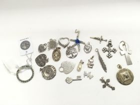A collection of over 20 silver pendants.
