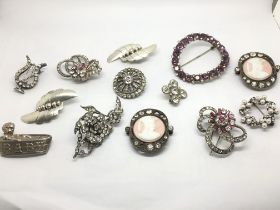 A collection of silver and paste brooches and pend