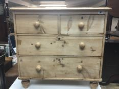 A small pine chest of drawers fitted with two short and two long drawers on turned feet.