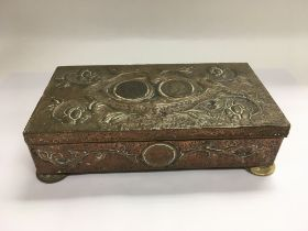 An Arts and Crafts copper card box inset with coin