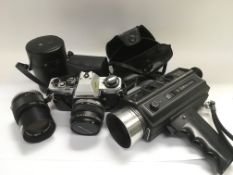 An Olympus camera and lenses plus a vintage Bell & Howell autoload 1216 camcorder with zoom lens.