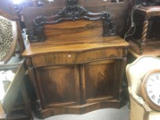 A William IV rosewood chiffonier with a raised back serpentine front above a drawer and cupboards