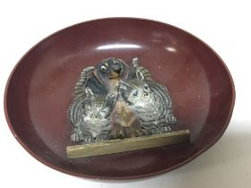 An unusual cold painted metal dish with raised cas