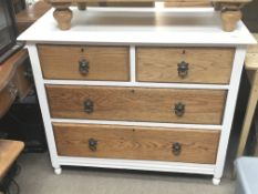 A white painted and oak small chest of drawers fitted with two short and two long drawers.