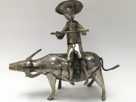 A white metal figure of an oriental man holding a stick whilst sat on a water buffalo.