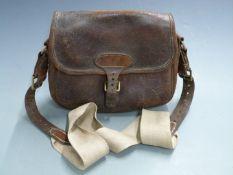 Vintage leather shotgun cartridge bag with canvas shoulder strap.