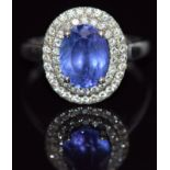 A 14k gold ring set with an oval cut tanzanite surrounded by two rows of diamonds, 4.5g,size Q