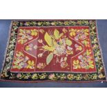A large rug with central abstract yellow motif on a wine ground, within a black border and floral