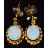 A pair of 9ct gold earrings set with an opal cabochon to each, 2.1g