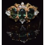 A 14k gold ring set with three oval cut green sapphires and diamonds, 3.9g,size N