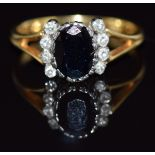 An 18ct gold ring set with an oval cut sapphire and eight diamonds, 3.6g,size O