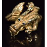 An 18ct gold ring in the form of a dragon with sapphire eyes, 10.7g, size O/P