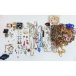 A collection of costume jewellery including necklaces, enamel and marcasite brooch, earrings, rolled