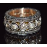 A large pierced gold ring set with diamonds in foiled settings with further diamonds to the edges