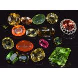 A collection of loose peridot, tourmaline, diopside, etc