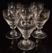 A set of six clear glass rummers raised on waisted stems, 14.5cm tall.