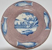 English Delft largeplate, London c1750, decorated with a scene of a lady feeding a bird before a