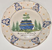 An 18th/19th century French Delft plate decorated with a jardinière, diameter 23cm