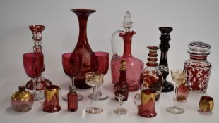 A collection of cranberry overlaid and cut glass items including a hallmarked silver mounted scent