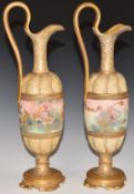 A pair of c1900Royal Doulton pedestal ewers hand decorated with flowers, H 35cm