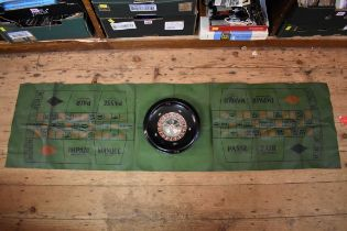 A vintage roulette wheel,24.5cm diameter, boxed and with playing mat.