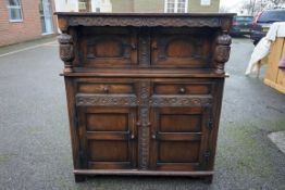 An old oak carved wall cupboard, 127cm wide x 52cm deep x 143cm high.Payment must be made in advance
