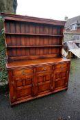 A reproduction oak dresser having rack back, 157cm wide x 52cm deep x 186cm high.Payment must be