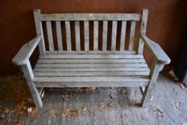 An old teak garden bench, 133cm wide x 63cm deep.Collection of this lot is strictly by appointment