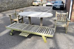 A teak garden table, 181 x 120cm; together with a pair of teak armchairs and a teak lounge chair.