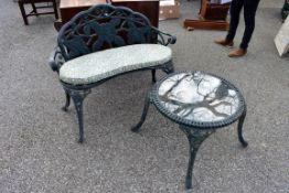 A cast iron kidney shaped garden bench; together with a matching table having glass top, 52 x 60cm.