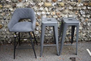 A grey upholstered bar stool; together with two other metal bar stools.