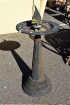 A cast iron sundial and bird bath.