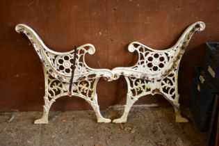 A pair of white painted cast iron bench ends, 73cm high x 60cm wide.