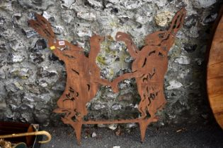 A steel garden ornament of fighting hares.