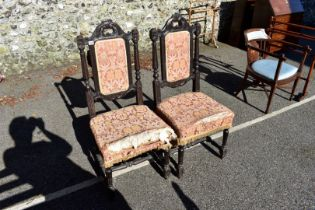 A pair of antique carved oak hall chairs, 110cm high.