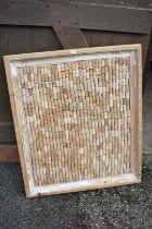 A framed display of bottle corks, 100cm wide x 84cm high.