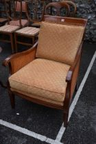 A reproduction bergere armchair.