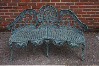 A green painted cast iron garden bench, 136cm wide.