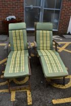 (LC) A pair of teak garden sun loungers.