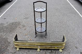 A brass fire fender, 103cm wide;together with a folding cake stand.