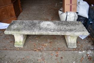 A reconstituted stone garden bench,having a pair of pedestal supports, 141cm wide.