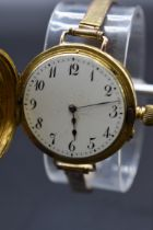 An Edwardian 18ct gold half hunter manual wind wristwatch, import mark 'B & M London 1907', 35mm, on
