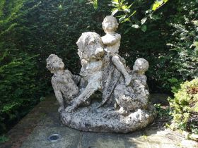 A composition stone group of a dog and children