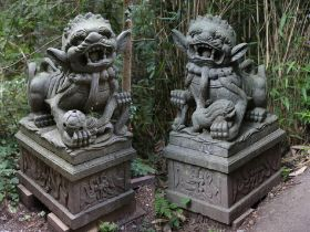 A pair of carved granite shi shi dogs on pedestals