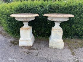 A pair of rare and unusually large Handyside foundry cast iron urns on pedestals