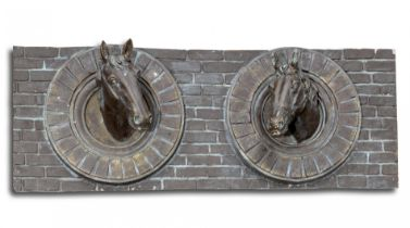 A bronzed fibreglass wall plaque of two horse's heads