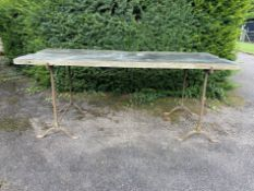 A rectangular slate table on iron trestle supports