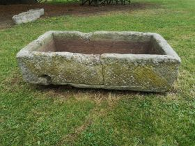 A rectangular carved stone trough