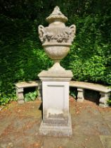 A composition stone finial on pedestal